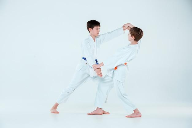 I due ragazzi che combattono all'aikido si allenano nella scuola di arti marziali. stile di vita sano e concetto di sport Foto Gratuite