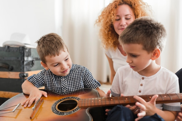Two boys playing guitar in front of their mother Free Photo
