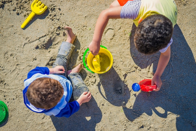 Two boys playing over sand with beach toys Premium Photo