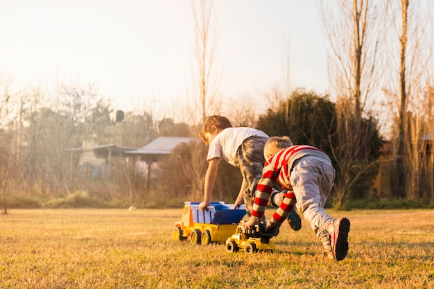 Two boys playing with toy vehicles on the green grass Free Photo