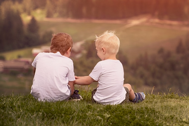 Two boys sit on the hill and talking cheerfull Premium Photo