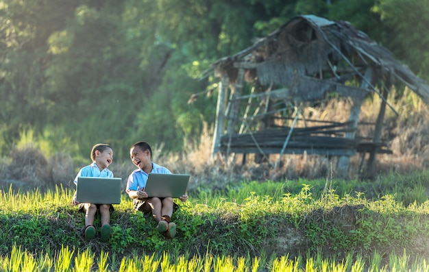 Two boys studying by online learning with laptop at outdoor, countryside of thailand Premium Photo