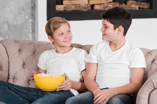 Two boys talking and sitting on couch Free Photo