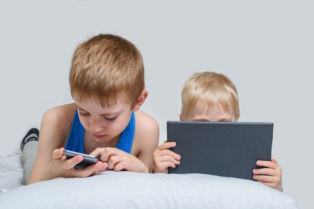 Two boys with gadgets are lying in bed. children use smart phone and tablet Premium Photo