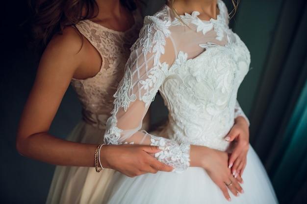 2人の花嫁が何かについてささやき、笑っています。ウェディングドレスの美しい繊細な女の子。 Premium写真