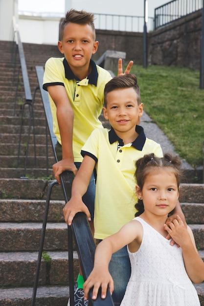 На лестнице стоят два брата и сестра. Premium Фотографии