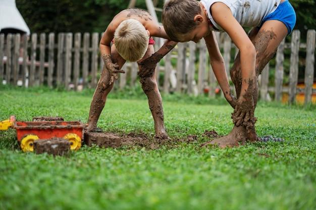 裏庭の外で泥で遊んでいる2人の兄弟が泥を自分たちのいたるところに広げています。 Premium写真