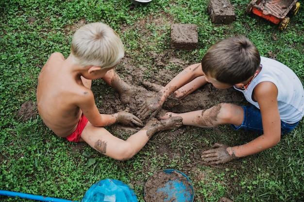 泥で遊ぶ2人の兄弟 Premium写真