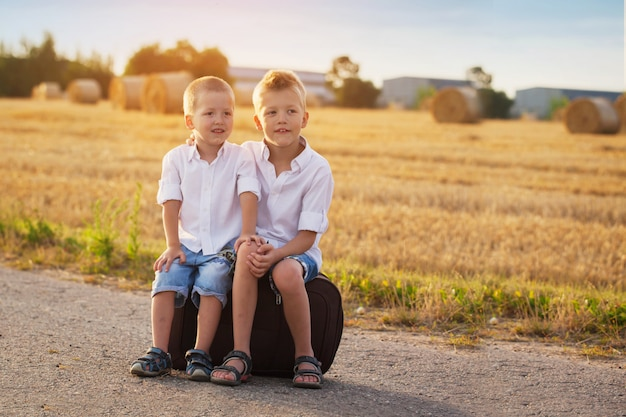 Two brothers sit on a suitcase on the road in the summer at sunset Premium Photo