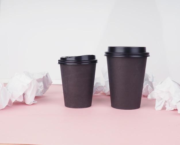 Две кофейные чашки из коричневой бумаги на розовом столе, рядом с ними скомканная бумага. Premium Фотографии