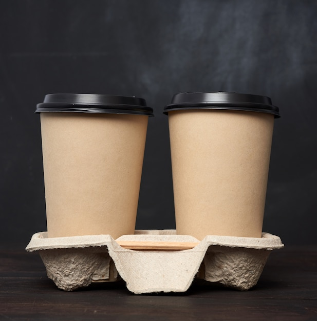 Two brown paper disposable cups with a plastic lid stand in the tray on a wooden table Premium Photo