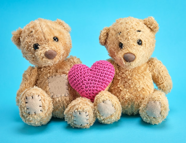 Two brown teddy bears hold a red knitted heart on a blue background Premium Photo