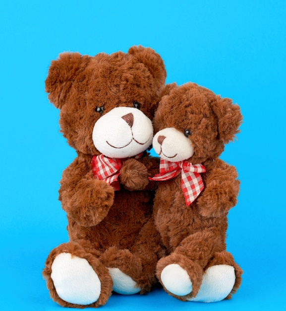 Two brown teddy bears with bows tied around their necks, a small bear sitting in the arms of a large one Premium Photo