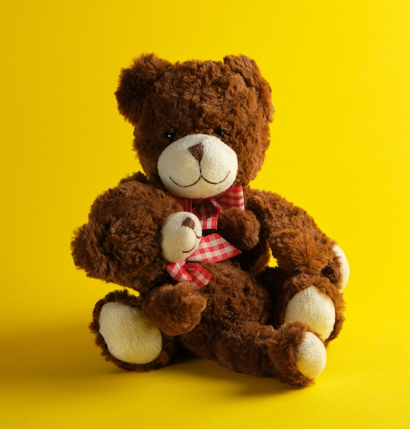 Two brown teddy bears on yellow Premium Photo