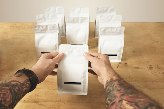 Two brutal tattooed roaster hands hold sealed package bag with tea or coffee ready for delivery and sale. Free Photo