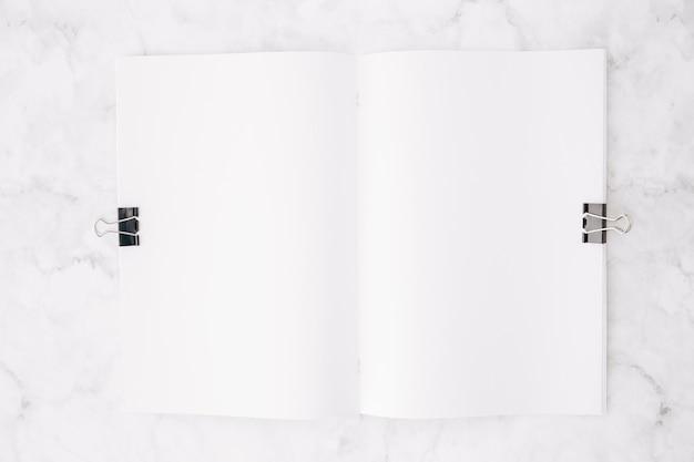 大理石のテクスチャ背景の上の白い紙の上の2つのブルドッグクリップ 無料写真