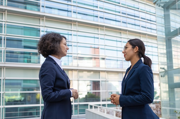Two business ladies discussing project near office Free Photo
