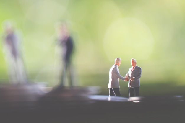 Two business man,saving and finance concepts. miniature people stand Premium Photo