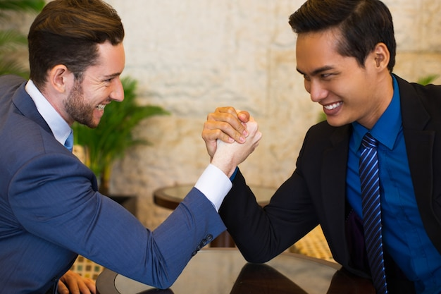 Two business men arm wrestling stubbornly in lobby Free Photo