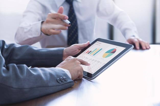 회의실에있는 두 사업가는 태블릿 화면에 워크 시트와 차트와 재무 성과 및 투자 분석에 대해 토론합니다. 프리미엄 사진