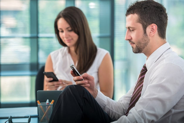 Two Business People Texting Premium Photo