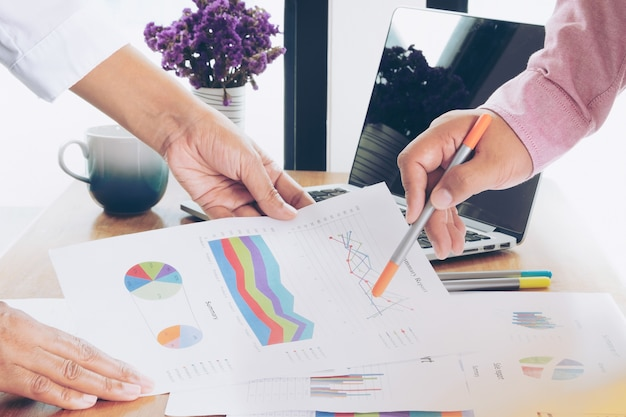 Two business people working in office and made decision on statistics of sale report Premium Photo