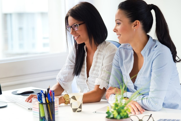 Two business woman working in office with computer. Free Photo