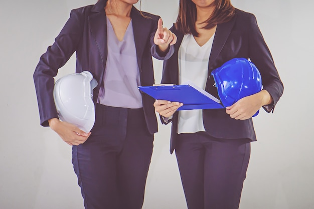 Two business women industrial engineers helmets with a tablet in hands Premium Photo