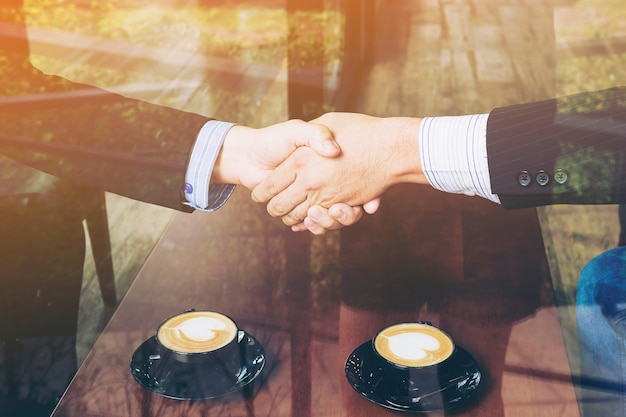 Two businessman shake hand in coffee shop Free Photo