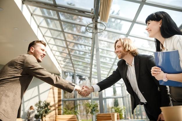 2人のビジネスマンが握手しています Premium写真