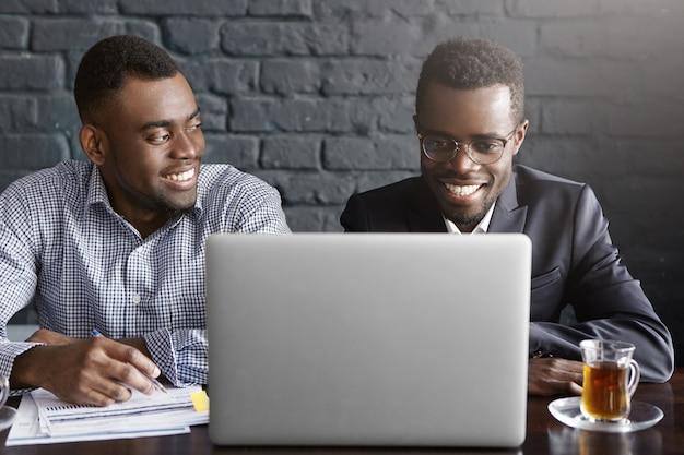 Due uomini d'affari discusing i dati finanziari sulla tavoletta digitale Foto Gratuite