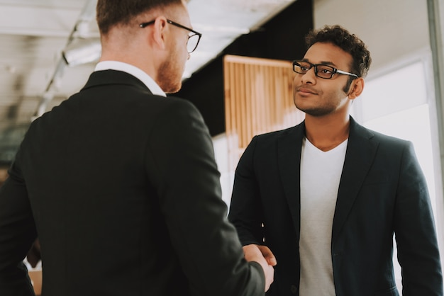 Two businessmen in glasses is shaking hands Premium Photo