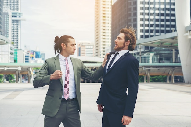 Two businessmen mad each other  trying to come to an agreement. Free Photo