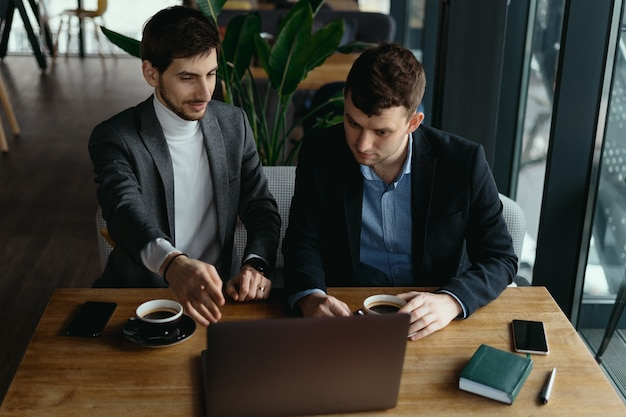 議論しながらノートパソコンの画面を指している2人のビジネスマン 無料写真