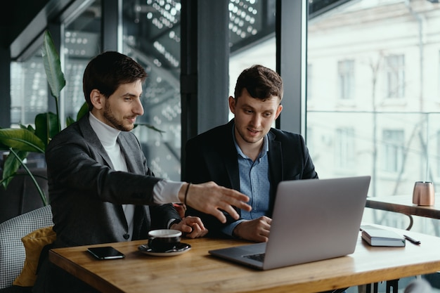 Two businessmen pointing laptop screen while discussing Free Photo