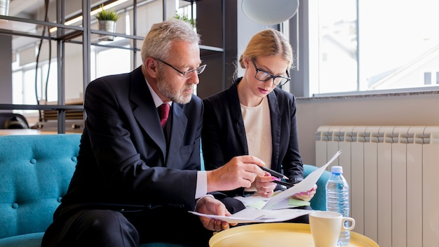 Two businesspeople discussing contract in the office Free Photo