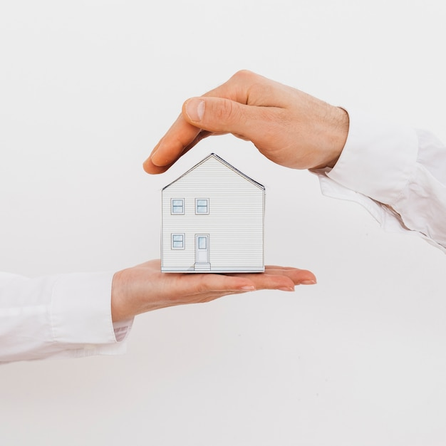 Two businesspeople hand's protecting miniature model house isolated on white background Free Photo
