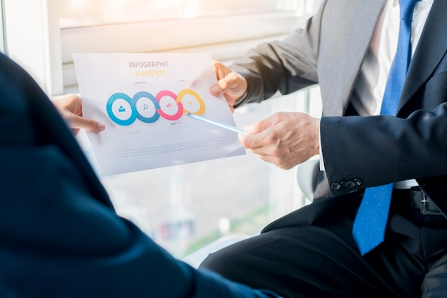 Two businesspeople holding infographic elements sheet Free Photo