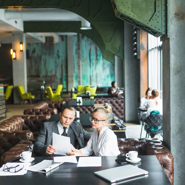 Two businesspeople looking at document in caf� Free Photo