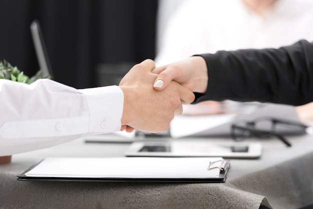 Two businesspeople shaking each other's hand over the clipboard on the desk Free Photo