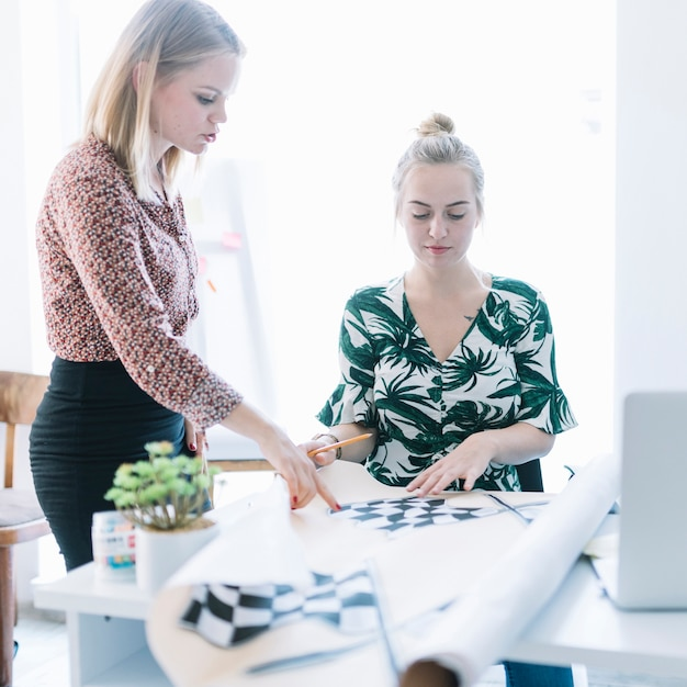 Two businesswomen preparing checkered flag on chart in office Free Photo