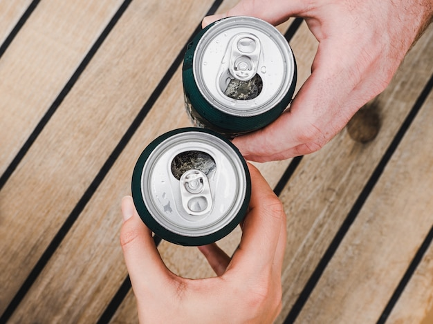 Two can of beer, female and male hands Premium Photo