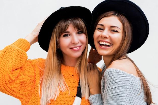 白の上に立って空気キスを送信する2つの屈託のない女の子 無料写真