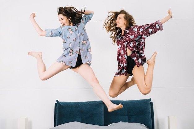 Two carefree woman jumping on bed Free Photo