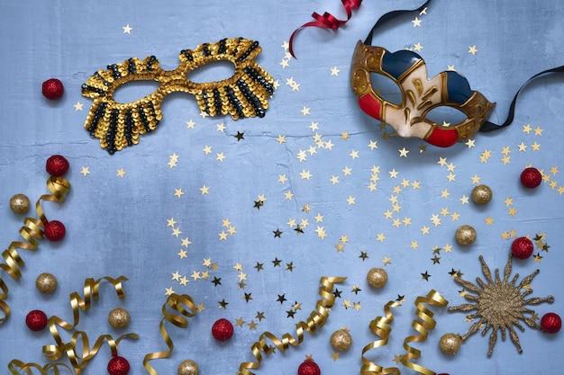 두 카니발 마스크, 색종이 별과 파란색 배경에 파티 깃발. 프리미엄 사진