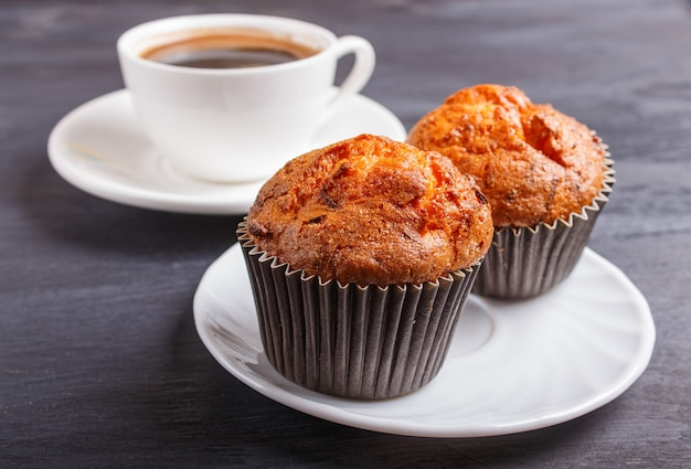 Two carrot muffins with cup of coffee on white plate on black wooden background Premium Photo
