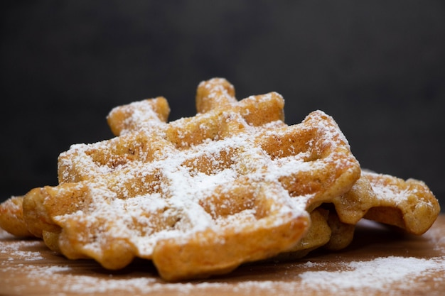 Two carrot waffles sprinkled with powdered sugar on a wooden board. Premium Photo