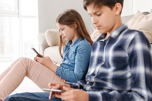 2人の白人の子供の女の子と男の子が自宅のソファの近くの床に座って、両方とも携帯電話を使用して Premium写真