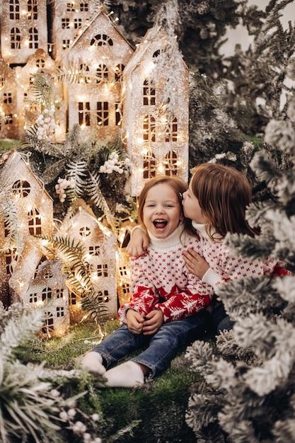 Due sorelle caucasiche posa per la fotocamera in una bellissima decorazione natalizia con molti alberi sotto la neve Foto Gratuite