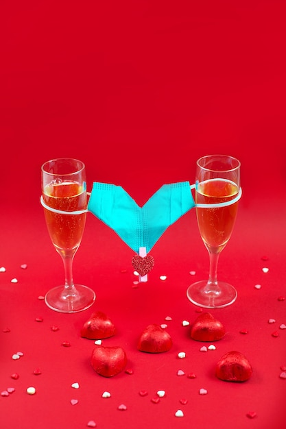 Two champagne glases, candy and medical mask valentine on red. Premium Photo